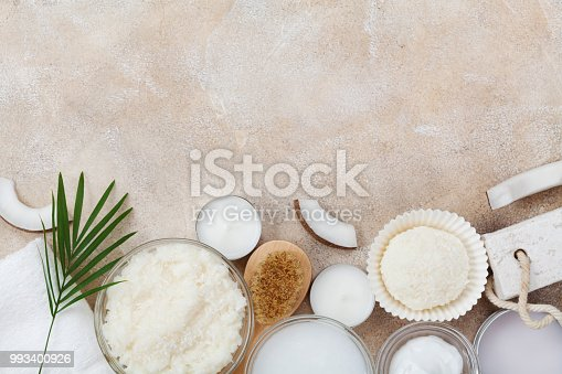 824824368 istock photo Spa setting from body care, wellness and beauty treatment. Coconut scrub, oil and cream on stone table top view. 993400926