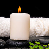 spa setting of  green branch fern, towels and candle on zen stones , closeup
