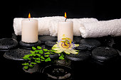 spa setting of passiflora flower, green branch fern and candles on zen stones with drops in ripple reflection water, closeup