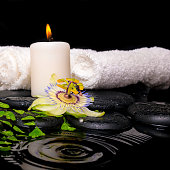 spa setting of passiflora flower, green branch fern, towels and candle on zen stones in ripple reflection water, closeup