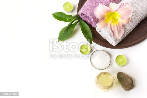 istock Spa setting of towel, flower on white background with copy space. Close up. Top view. 909927920