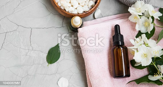 Spa setting with skincare products, oil bottle, towels, bath salt and jasmine flowers
