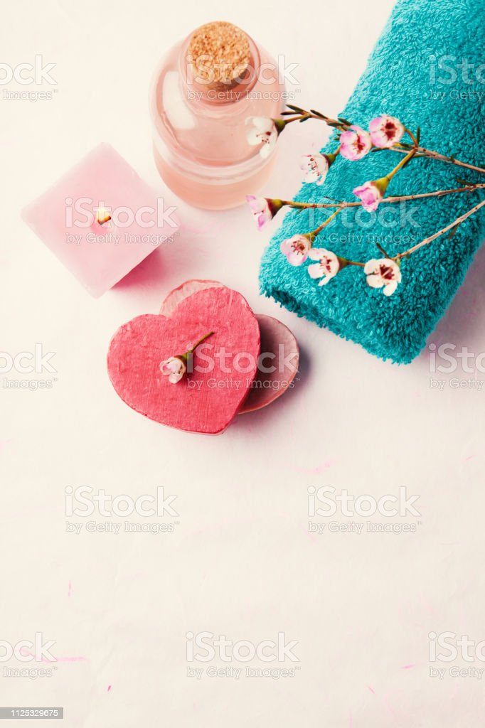 Spa setting with towel, soap, waxflowers and candle stock photo