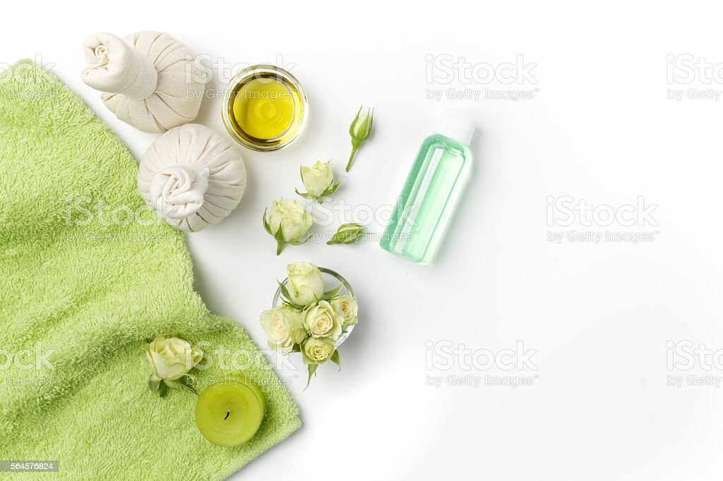Spa settings. Fresh roses in a plate and herbal compress stock photo