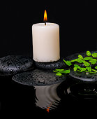spa still life of green leaf fern with drop and candle on zen stones in ripple reflection water, closeup