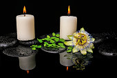 spa still life of passiflora flower, green leaf fern with drop and candles on zen stones in reflection water, closeup