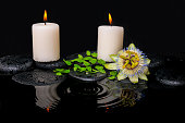 spa still life of passiflora flower, green leaf fern with drop and candles on zen stones in ripple reflection water, closeup