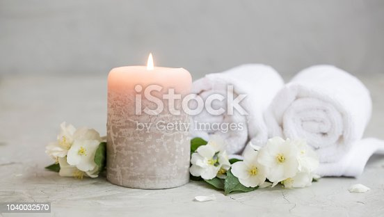 Spa still life with candle, white jasmine and towels, spa setting