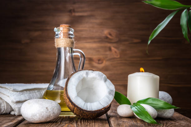 spa still life with coconut, massage oil and candle on a wooden background - oleo palma imagens e fotografias de stock