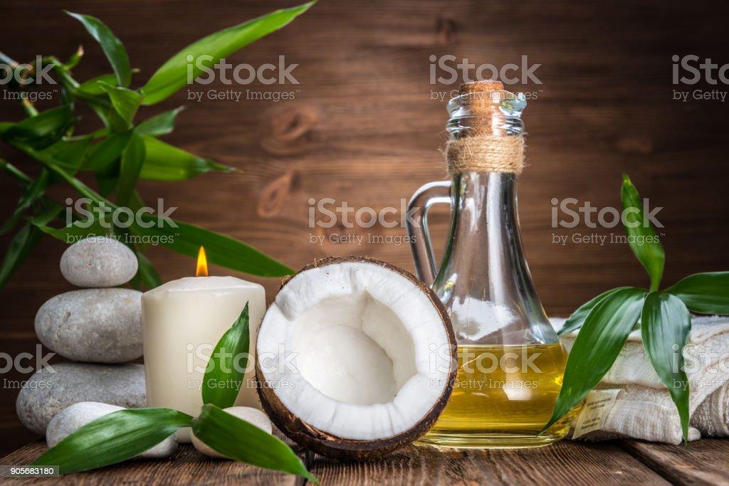 Spa nature morte aux noix de coco, huile de massage et bougie sur un fond en bois - Photo