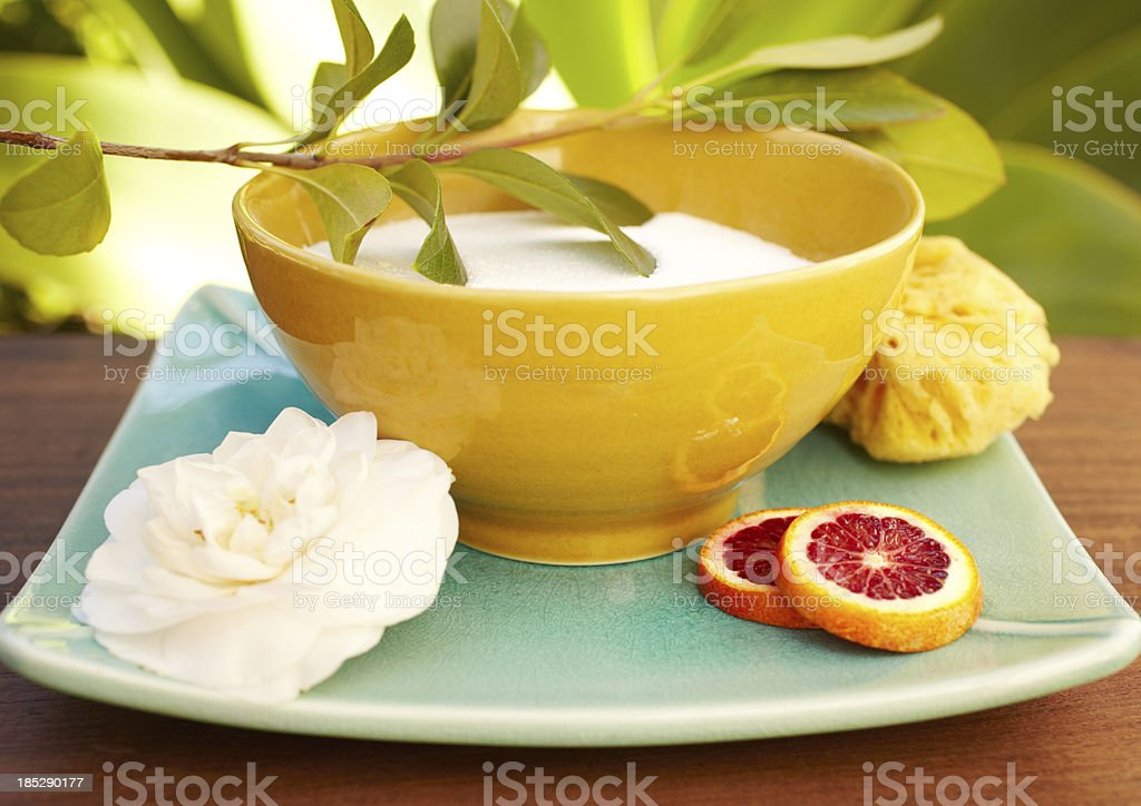 Spa still life with moisturizer, exfoliation sponge, flower and orange royalty-free stock photo
