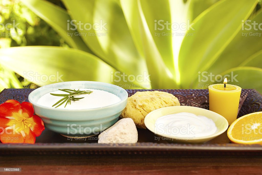 Spa still life with moisturizer, scrub, exfoliation sponge and candle royalty-free stock photo