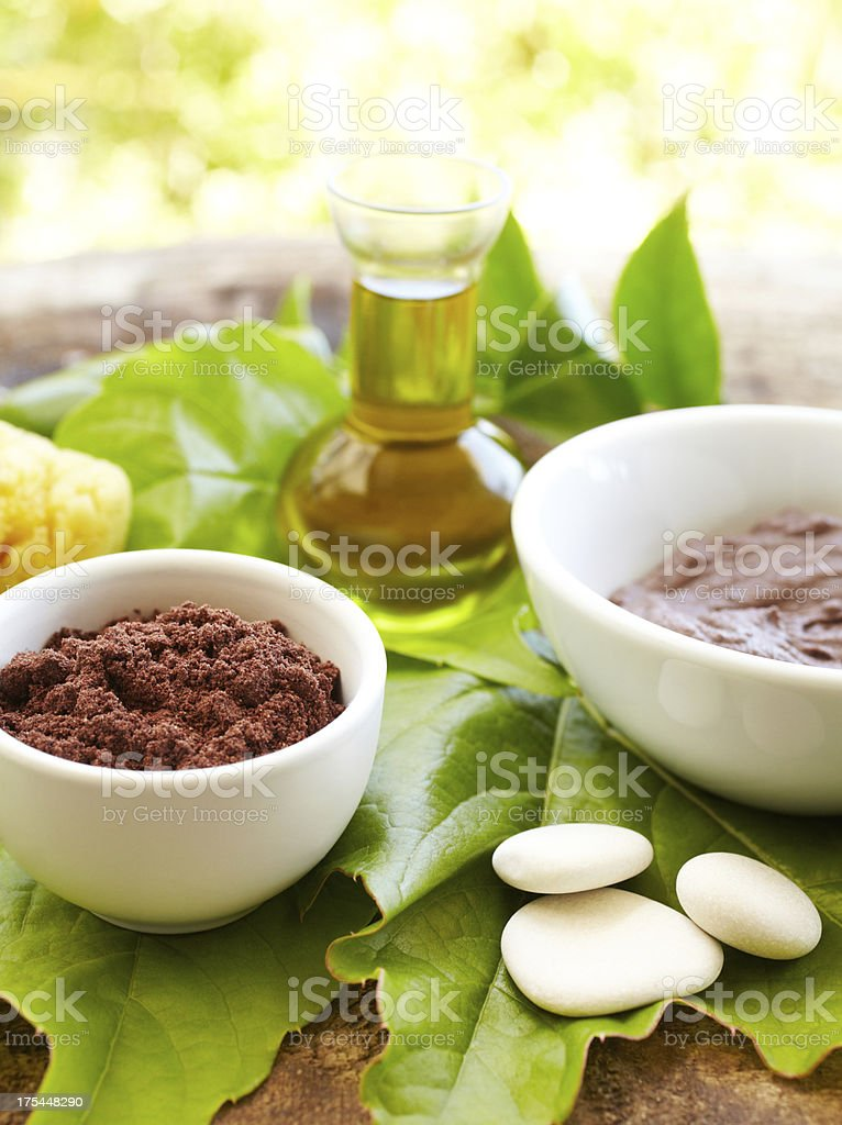 Spa still life with mud mask and massage oil stock photo