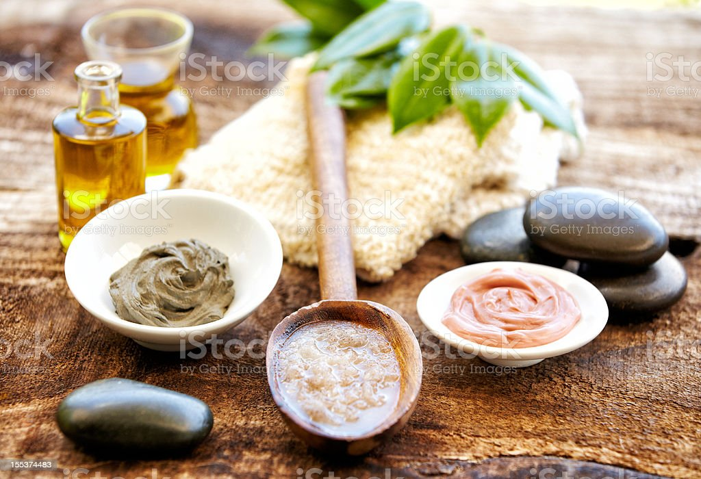 Spa still life with mud mask, salt scrubbing, massage oil stock photo