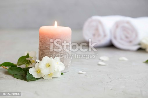 Spa still life with scented candle, jasmine flowers and towels in the background