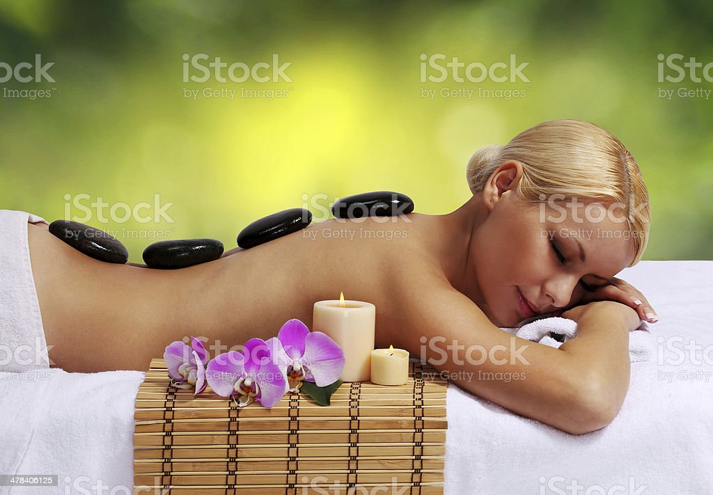 Spa Stone Massage. Beautiful Blonde Woman Getting Hot Stones Massage stock photo