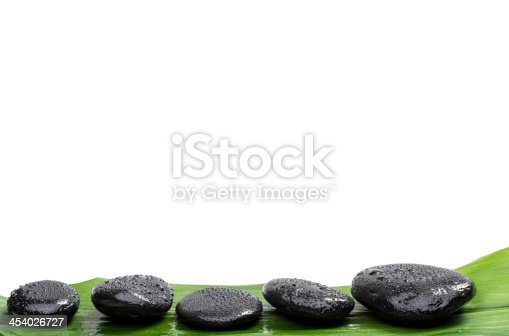 istock Spa stones   on green leaf, isolated background 454026727