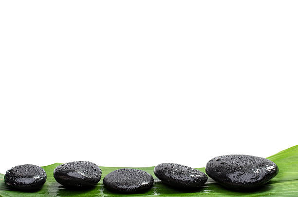 Spa stones   on green leaf, isolated background stock photo