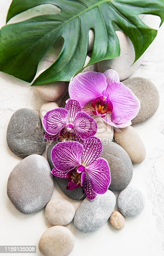 Spa stones with orchid flowers on a white marble background