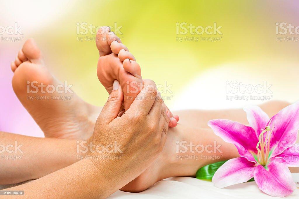 Spa therapist doing foot massage stock photo