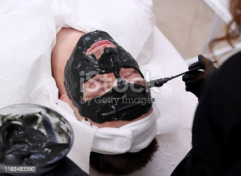 Cleaning the face of a man in a beauty salon. Spa therapy for men receiving facial black mask.