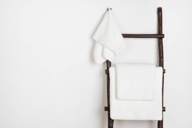 spa handtücher hängen vintage holz trittleiter isoliert auf weiss - sauna textilien stock-fotos und bilder