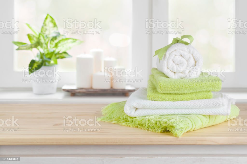 Spa towels on wooden table over blurred salon window background stock photo
