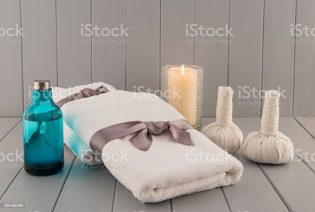 Spa Towels with Herbal Massage Balls, Oil, and Candle stock photo