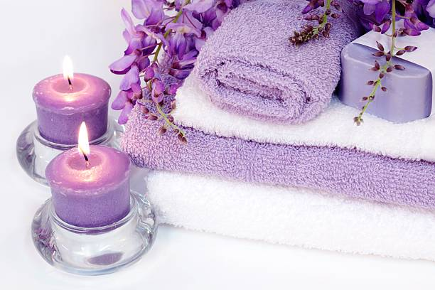 Spa Tranquility with purple candles, towels, wisteria and soap stock photo