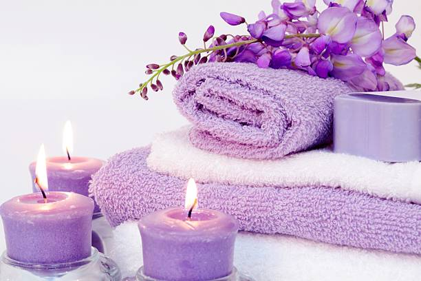 Spa Tranquility with purple towels, candles and flowers stock photo