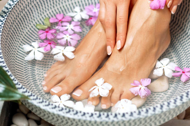 spa treatment and product for female feet and foot spa. foot bath in bowl with tropical flowers, thailand. healthy concept. beautiful female feet, legs at spa salon on pedicure procedure. - pedicure foto e immagini stock