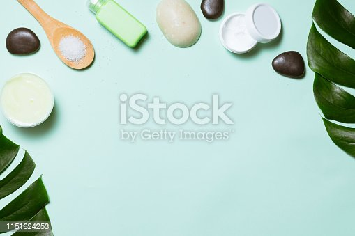 Spa treatment on pastel background with bamboo stalk and green leaves, flat lay. Top view of beauty bath background for body care and wellness
