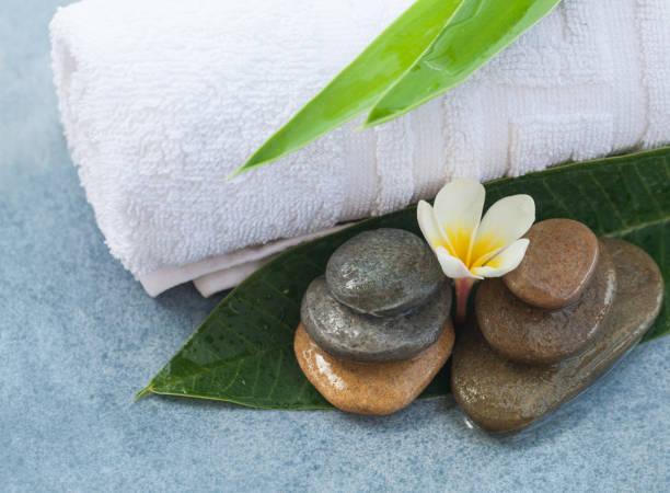 wellness tropische blume mit steinen für massageraum - steingut geschirr stock-fotos und bilder