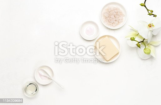 Spa white background with blank space for a text, flat lay composition with various natural cosmetics products decorated with white orchid