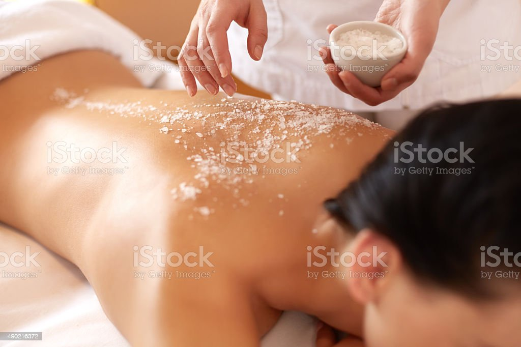 Spa Woman. Brunette Getting a Salt Scrub Beauty Treatment stock photo