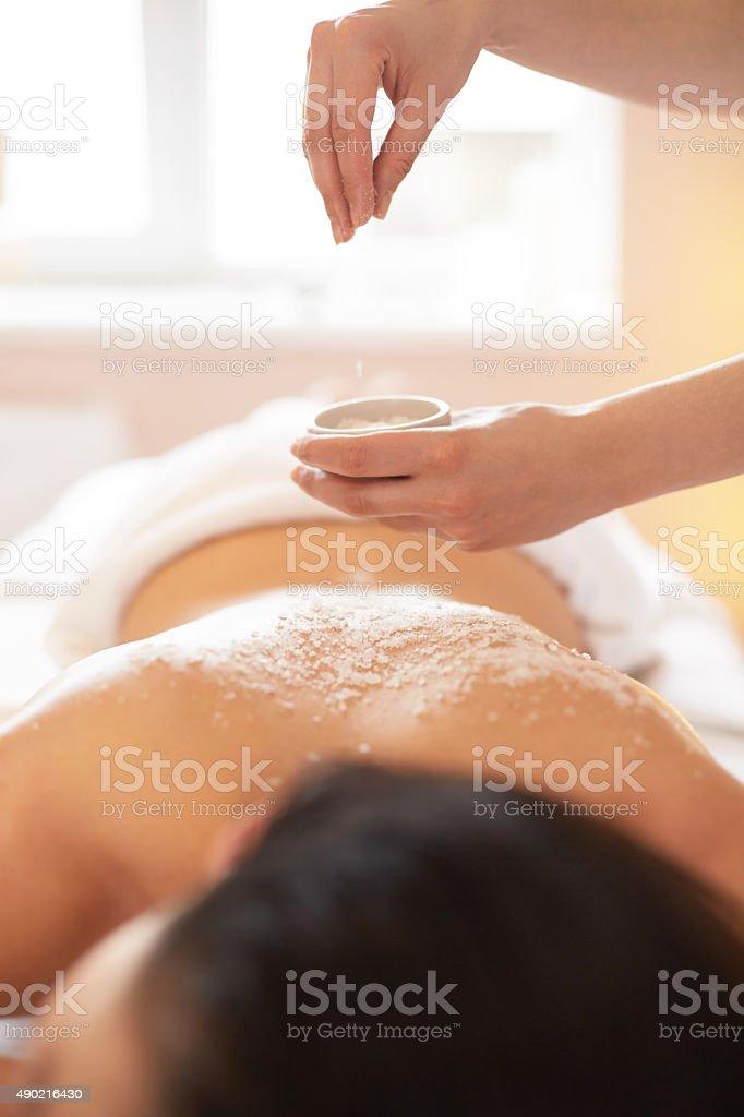 Spa Woman. Brunette Getting a Salt Scrub Beauty Treatment stock photo