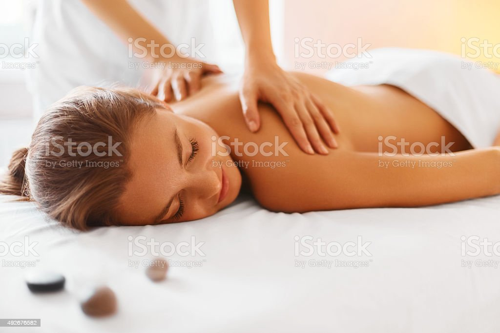 Spa Woman. Female Enjoying Massage in Spa Centre. Spa woman. Female enjoying relaxing back massage in cosmetology spa centre. Body care, skin care, wellness, wellbeing, beauty treatment concept. 2015 Stock Photo