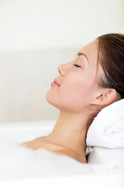 frau entspannenden spa - badewannenkissen stock-fotos und bilder