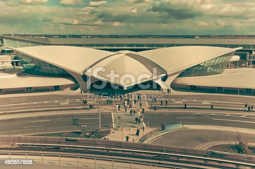 Vintage filter style view of landmark TWA Flight Center at John F. Kennedy International Airport in Queens, New York, City with unidentifiable people in scene