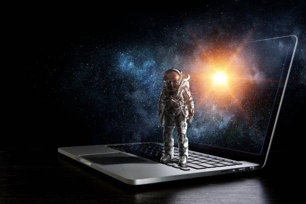 Space explorer and laptop. Mixed media stock photo