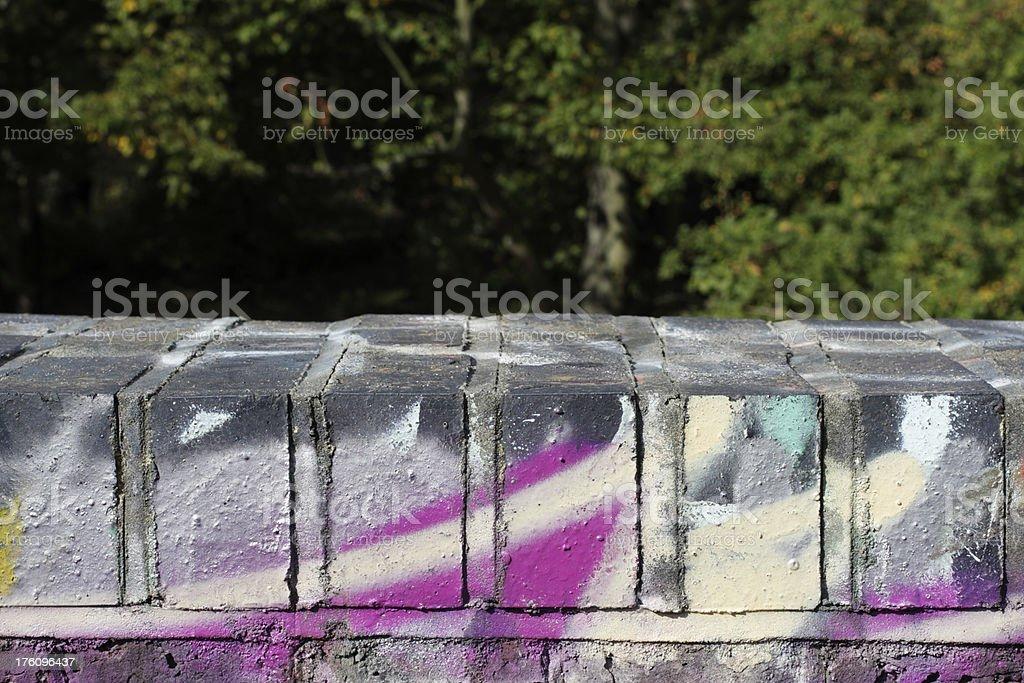 Graffiti sprayed on five top bricks of a wall stock photo