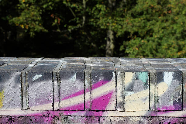 graffiti sprayed on five top bricks of a wall - whiteway graffiti stock photos and pictures