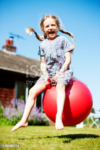 A young girl playing with her spacehopper. Smiling and looking at the camera