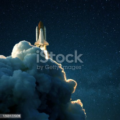 istock Space rocket launches into space against a starry blue sky. Ship shuttle with clouds of smoke 1203122028
