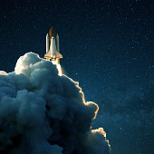 Space rocket launches into space against a starry blue sky. Ship shuttle with clouds of smoke