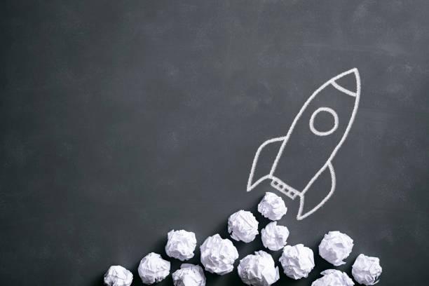 rakete auf tafel - zerknittertes papier idee kreativität - anfang stock-fotos und bilder