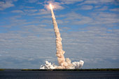 NASA Space Shuttle Atlantis moving through a cloud after launch