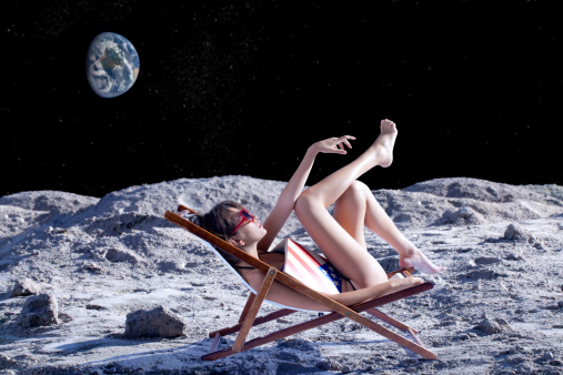 Woman resting and tanning over a sun chair on moon's surface.