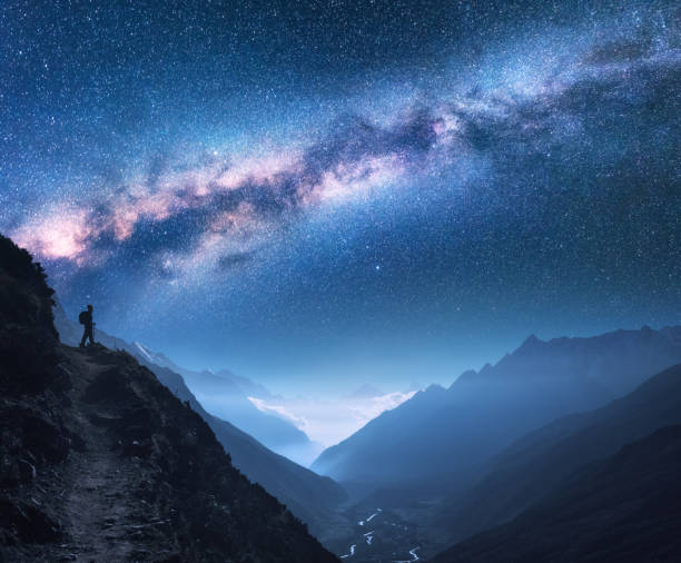 space with milky way, girl and mountains. silhouette of standing woman on the mountain peak, mountains and starry sky at night in nepal. sky with stars. trekking. night landscape with bright milky way - den belitsky foto e immagini stock