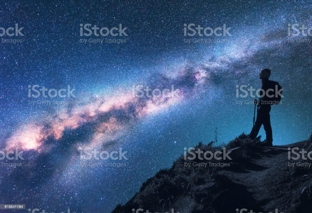 Space with Milky Way. Silhouette of a woman with backpack at night. Girl on the mountain peak and starry sky. Sky with stars and woman. Trekking. Night landscape with bright milky way and traveler stock photo
